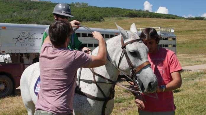 Argentine player Nacho Novillo Astrada helps his son Santos with his horse.