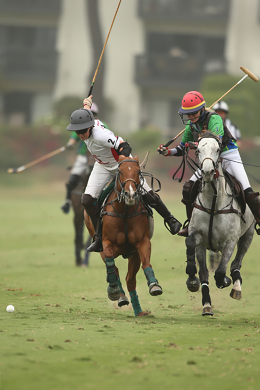 Rancho Polo's Piers Bossom prepares for a booming shot down field, BFBST Law's Leigh Brecheen hustles to defend.