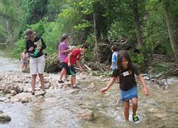 Children playing in a creek bed with friends