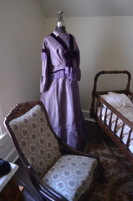 Elizabeth's rocker and cradle, with a period dress in between. Photo courtesy of Sherrie Horn.