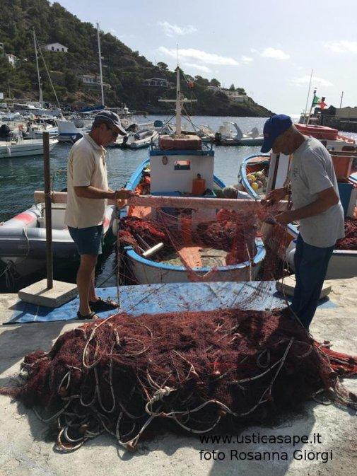 pescatori controllano e sistemano le reti