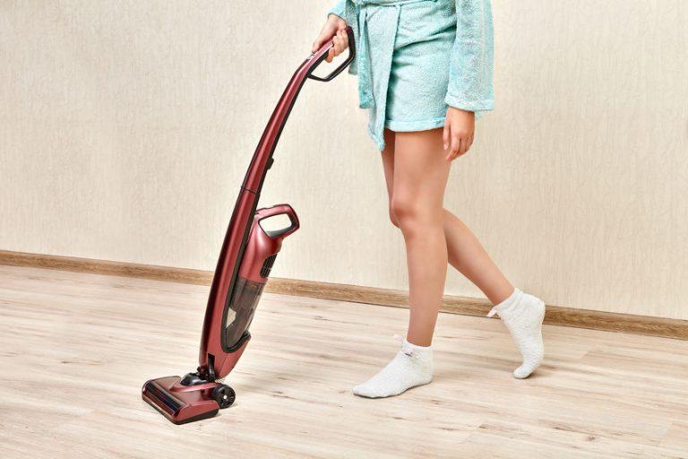 Donna che pulisce con la scopa elettrica