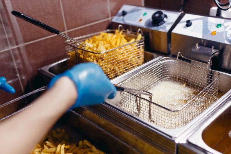 Persona che utilizza una friggitrice professionale