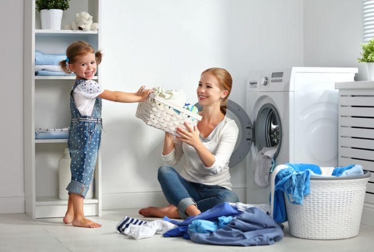 Donna con cesta dei panni vicino a una lavatrice