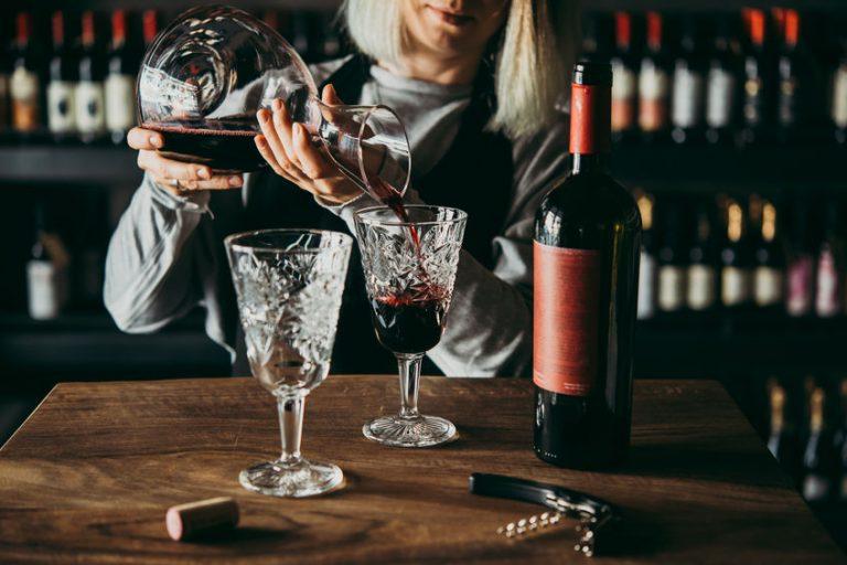 Donna che versa il vino dal decanter