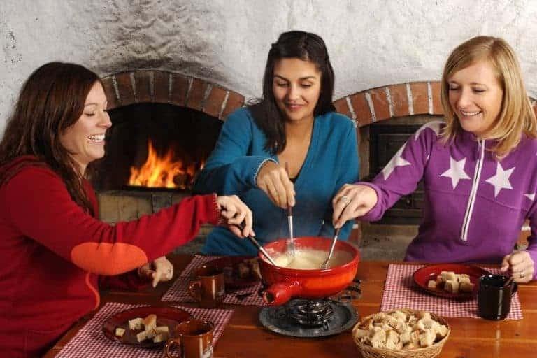 Tre donne intorno a un set da fonduta per formaggio