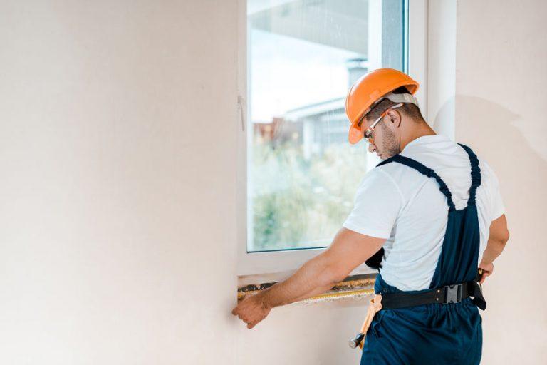 Lavoratore che prende la misura di una finestra