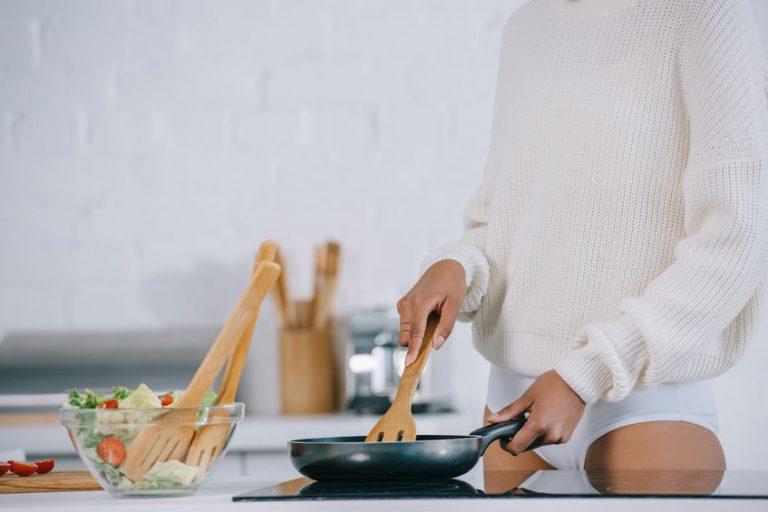 Persona che usa una padella sulla cucina a induzione