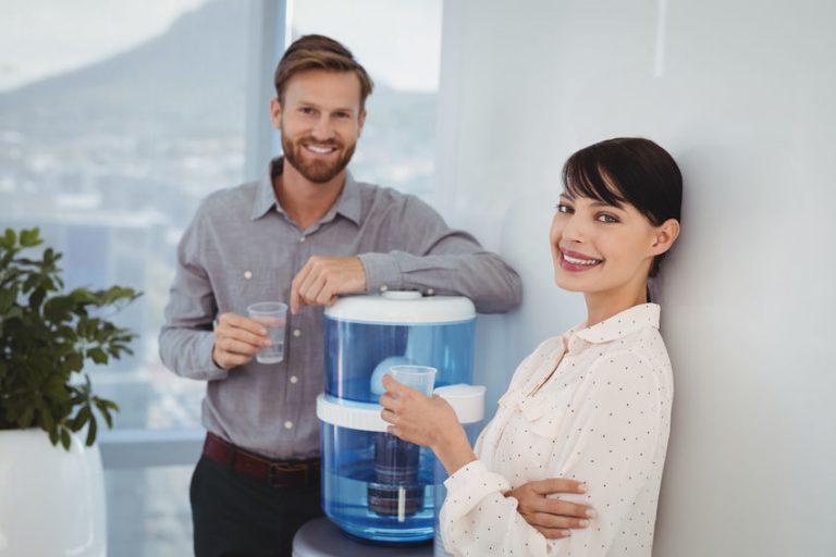 Uomo e donna vicino a un dispenser di acqua