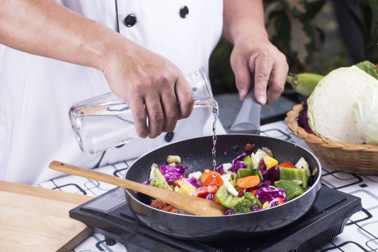 Chef cucinando in una padella per induzione