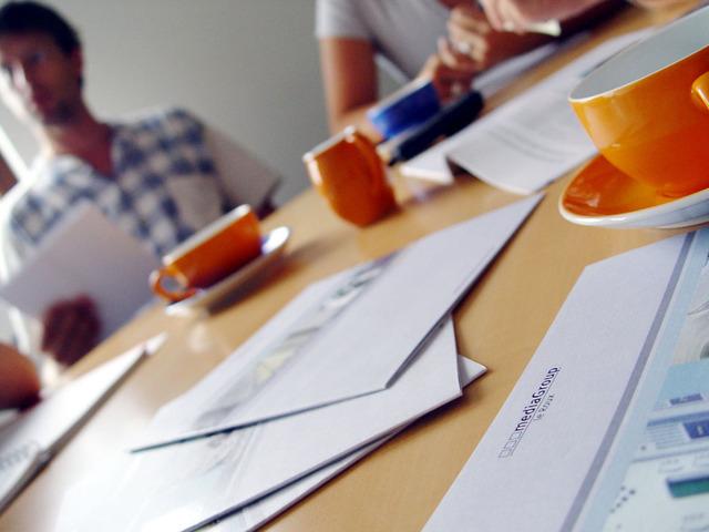 Flera personer sitter runt ett bord och har möte. En del papper/broschyrer ligger på bordet. Det står fler orangea kaffekoppar på bordet.