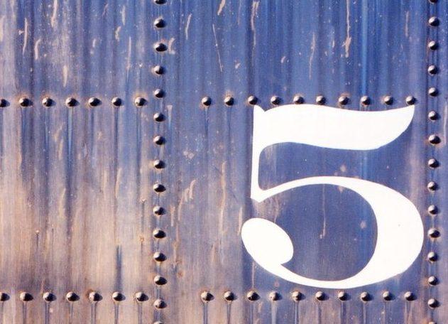 Bild på plåt med många bultar och en stor vit 5:a ritad på.