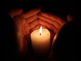 Hands cupping a candle flame in the dark