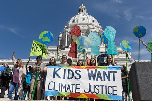 "Crowd of kids in front of government building with sign reading ""Kids Want Climate Justice"""