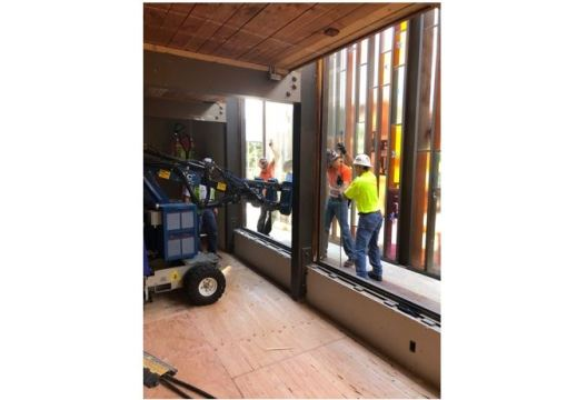 Three men and a machine installing a window in the sanctuary