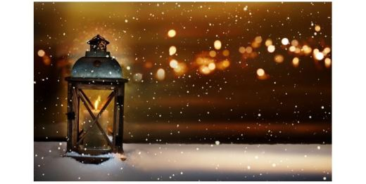 Burning candle lantern in a winter landscape with golden bokeh in the night