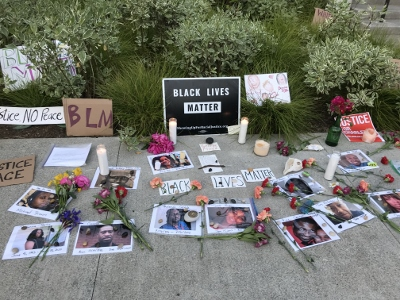 """Signs (""""Black Lives Matter""""), photos, candles and flowers laid out on sidewalk"""