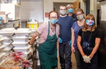 Five smiling people, wearing masks, in an industrial kitchen, with stacks of to-go boxes