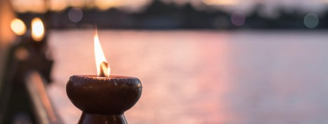 Photograph of a flaming chalice with a background of sunset reflecting off water