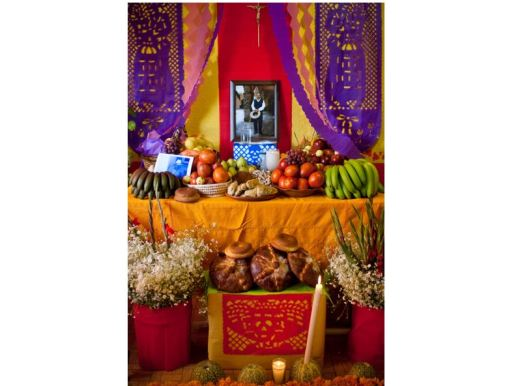 A Dia de los Muertos altar with fruits, flowers, breads, photographs and candles