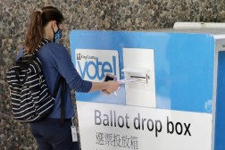 Person inserting their ballot into a King County ballot drop box