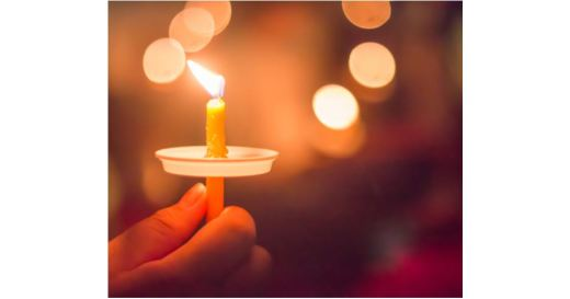Hand holding a small candle with a drip catcher - warm colors