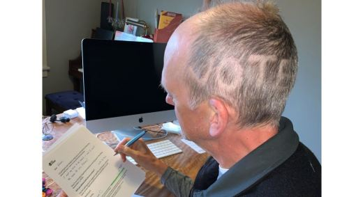 "Steve C sitting at a desk with ""VOTE"" shaved into the left side of his head"