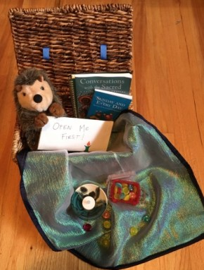 """Open wicker basket with stuffed hedgehog, books, chalice, cloth and """"jewels"""""""