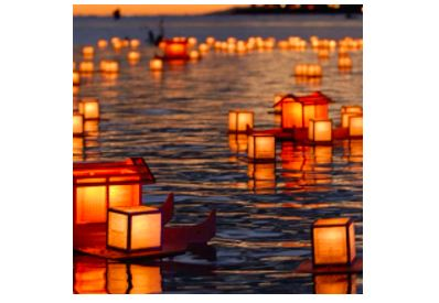 Scores of Japanese-style lanterns floating on water at sunset
