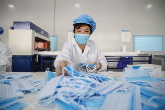A masked woman works on the production line of surgical masks at Yilong medical instruments Co., Ltd amid the coronavirus outbreak on April 16, 2020 in Zunyi, Guizhou Province of China