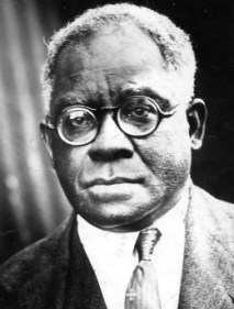 A Black man with grey hair and glasses wearing a suit and tie