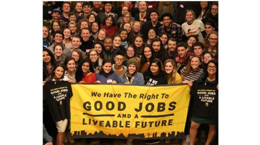 "A crowd of smiling young people holding a banner: ""We Have The Right To GOOD JOBS AND A LIVEABLE FUTURE"""