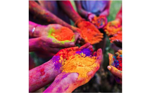 The cupped palms, filled with brightly colored powders, of 7 people standing in a circle, their arms smeared with color