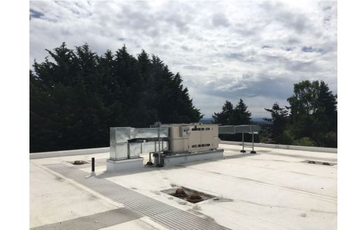 Metal ductwork and apparatus on the UUC roof - tree tops and clouds in background.