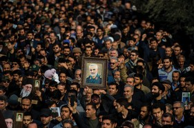 Protesters hold up an image of Qassem Soleimani, an Iranian commander, during a demonstration
