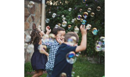 Kids running through and batting at soap bubbles