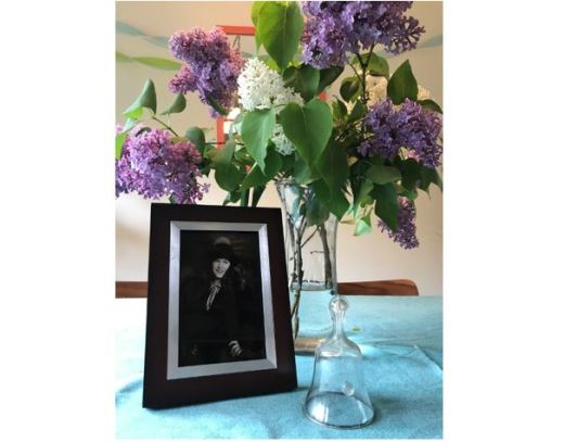 Framed photo of woman, vase of lilacs, and glass bell