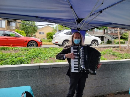 Dwight, masked, and playing his accordion under the blue canopy set up in the parking lot