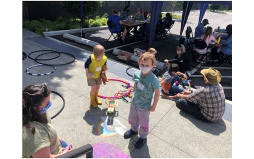 Kids playing in the sun and adults visiting in the shade at UUC Art and Game Day, summer 2021