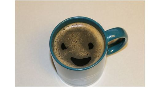Photo of a mug full of coffee where the bubbles form a smiley face
