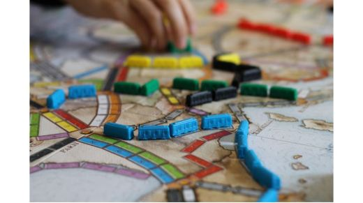 A colorful board game with lots of little passenger train car tokens and a hand moving touching one of them