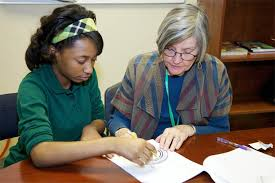 Young girl and older woman working together on school assignment