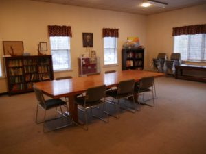 Room with board style table, chairs and bookcases.