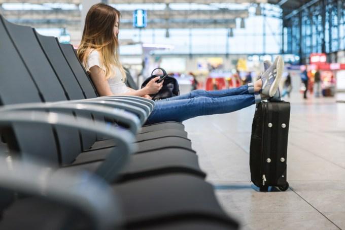 空港のロビーで飛行機を待つ女性