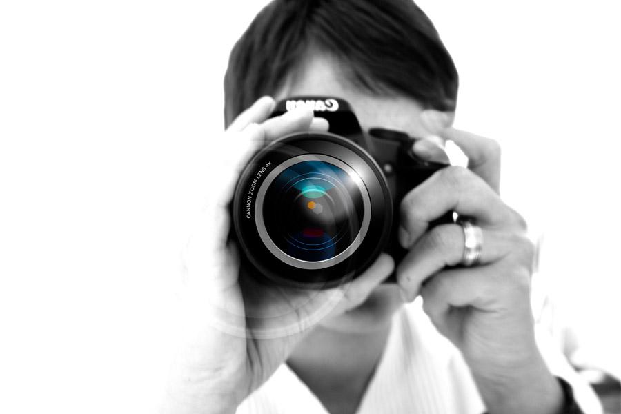 レンズフレアと一眼レフカメラを構える男性