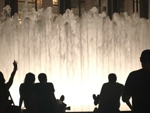 People sitting in from of fountain at Lincoln Center at night
