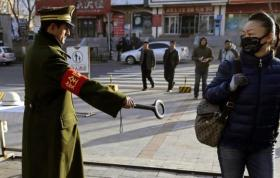A pedestrian reacts as a security officer holds out a detector on a street in Urumqi