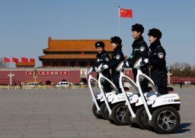 Police offices ride on motorized vehicles ahead of the opening session of Chinese People's Political Consultative Conference at Tiananmen Square in Beijing