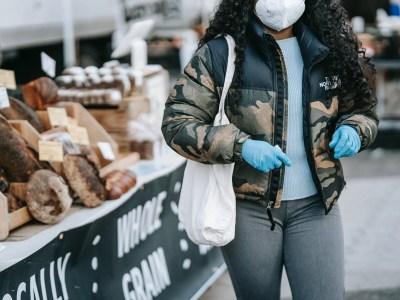 black woman in mask walking by street bakery