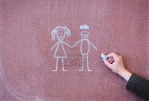 14167089-boy-and-girl-holding-hands-drawing-with-chalk-on-blackboard